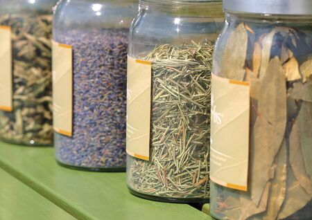 Close-up of dried herbs in glass jars