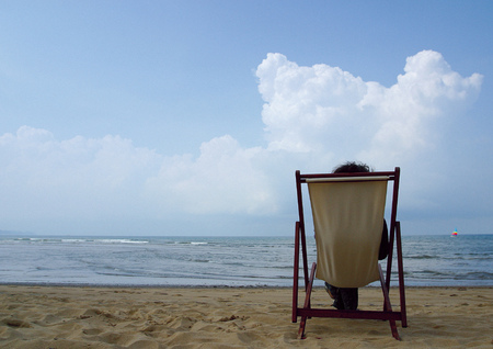 Rear view of a person sitting in a chair on the beach Stock Photo - 1943821