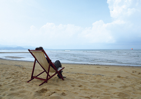 reclining chair: Rear view of a person sitting in a chair on the beach Stock Photo