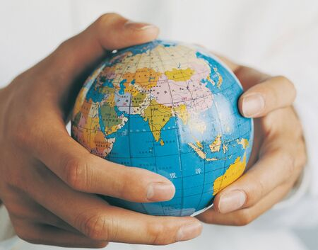 world at your fingertips: Close-up of a miniature globe in a mans hands Stock Photo