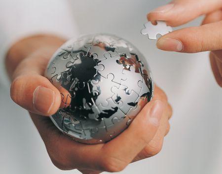 mans: Close-up of a metal jigsaw ball in a mans hands