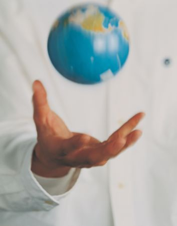 world at your fingertips: Midsection view of a man throwing a miniature globe