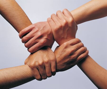 two people with others: Close-up of two people holding each others wrists