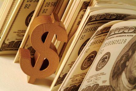 Close-up of a dollar sign beside dollar bills