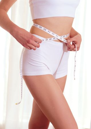 Mid section view of a woman measuring her waist Stock Photo