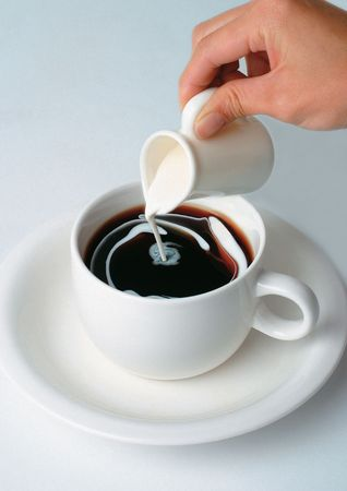 High angle view of a person pouring cream in a cup of coffee Stock Photo