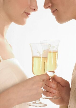 Side profile of a young couple holding champagne glasses Stock Photo