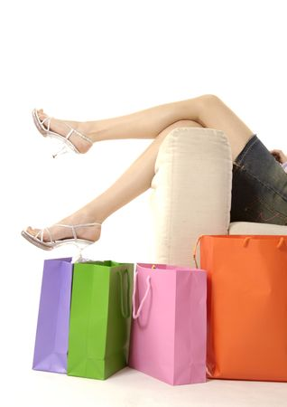 View of a woman lying on a couch with shopping bags placed beside it