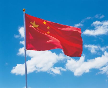 unfurl: Low angle view of the Chinese flag on a pole
