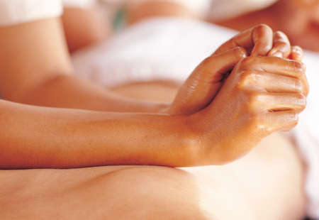 Close-up of a womans hands massaging a persons back Stock Photo