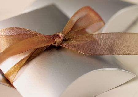 High angle view of a silver gift box tied with brown ribbon