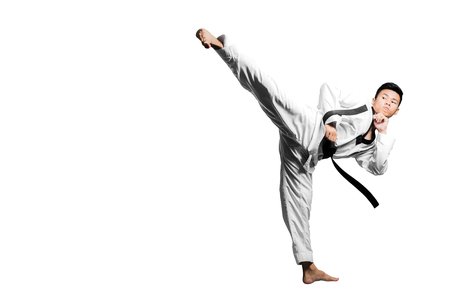 Portrait of a handsome asian man kick with taekwondo black belt . Isolated on white background with copy space Stock Photo