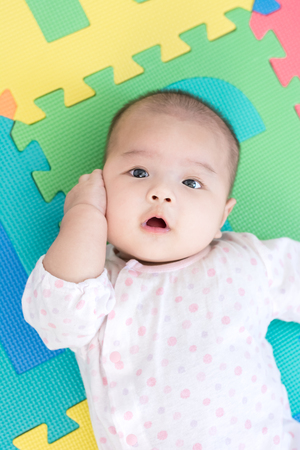 Portrait of a little adorable newborn infant baby girl lying on back on colorful eva foam and looking in camera indoors