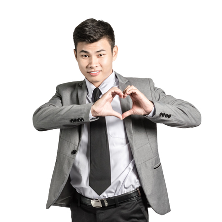 Portrait of a young businessman making a heart with his hands. Isolated on white background