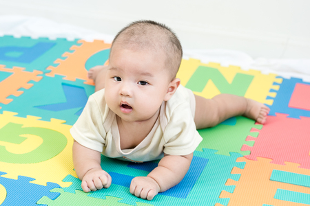 Portrait of a little adorable newborn infant baby girl lying on the tummy on colorful eva foam and looking in camera indoors