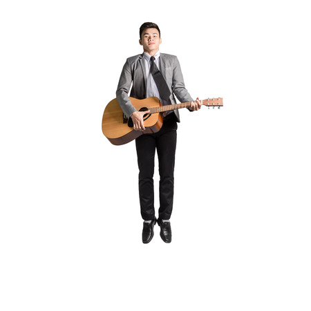 Portrait of a young business man jumping with guitar. Isolated on white background with copy space