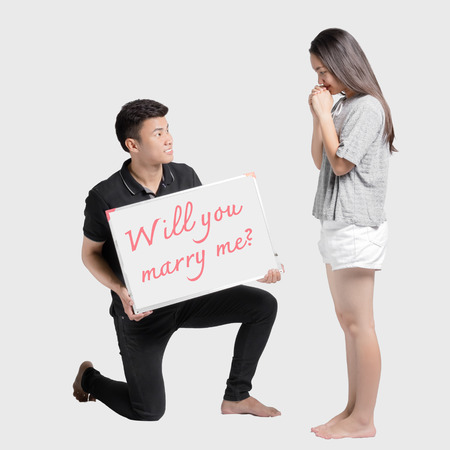 Will you marry me? Full length of man making proposal to his girlfriend while standing at his knee and showing a message board. Isolated on grey background Stock Photo