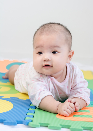Portrait of a little adorable newborn infant baby girl with saliva lying on the tummy on colorful eva foam and looking in camera indoors