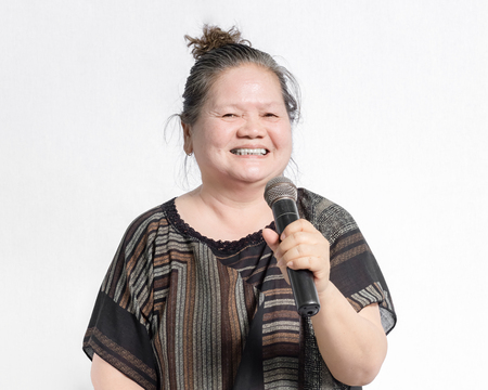 portrait of a mature woman sing a song on microphone. Isolated on grey background