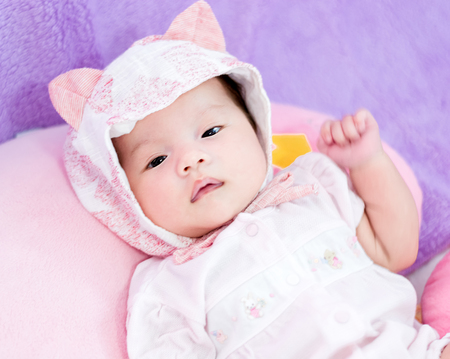 Portrait of a little adorable infant baby girl with hat lying on the back on the pillow