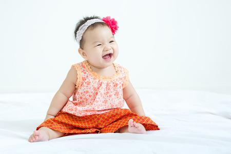 Portrait of a little adorable infant baby girl sitting on the bed and smiling to the right side with copyspace