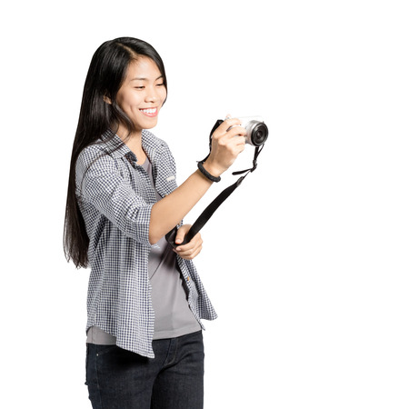 Portrait of a young asian woman traveler photography hipster with camera. Isolated on white background