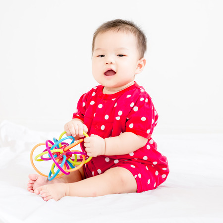 Portrait of a little adorable infant baby girl sitting on the bed and smiling to camera with bites toy