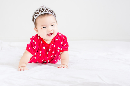 Portrait of a little adorable infant baby girl sitting on the bed with copyspace