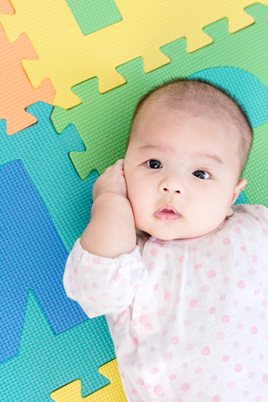 Portrait of a little adorable infant baby girl lying on back on colorful eva foam and looking in camera indoors Stock Photo