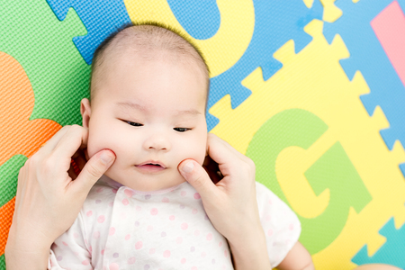 Parent pinch the cheeks a little adorable newborn infant baby girl that lying on the back on colorful eva foam indoors