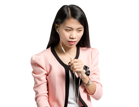 Portrait of a young business woman smiling with earbuds / headphone for listening to music or talking on smart phone. Stock Photo