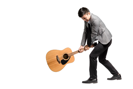 thai musical instrument: Portrait of a young business man smashing his guitar. Isolated on white background with copy space and clipping path Stock Photo