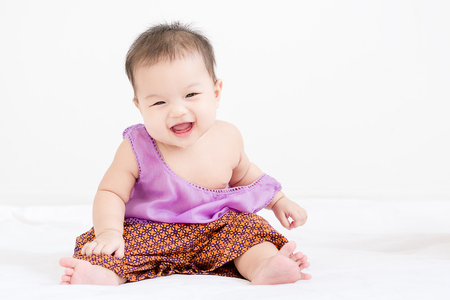 Portrait of a little adorable infant baby girl sitting on the bed and smiling to camera with copyspace Stock Photo