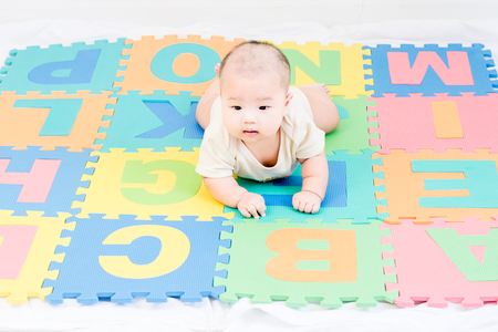 Portrait of a little adorable infant baby girl lying on the tummy on colorful eva foam indoors