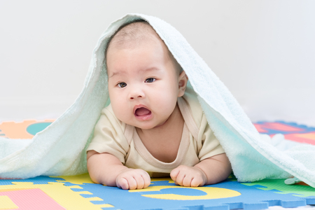 Portrait of a little adorable infant baby girl with blanket lying on the tummy on colorful eva foam indoors