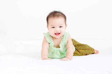 Portrait of a little adorable infant baby girl with saliva lying on the tummy on bed and looking in camera indoors