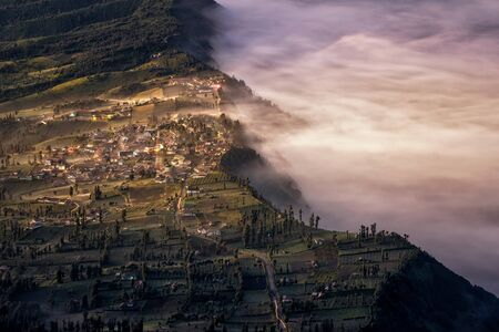 tengger: Touch of morning light on fog and mist at Cemoro Lawang village in Bromo tengger semeru national park, East Java, Indonesia Stock Photo