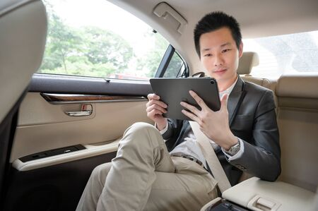 Handsome asian businessman working with tablet. Young executive manager Full concentration at work while sitting in the car. Standard-Bild