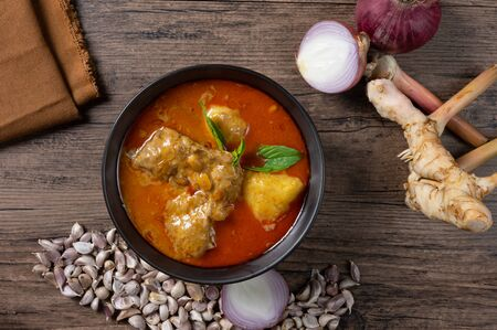 Chicken massaman curry in black bowl with herb and spices on wooden background. Thai authentic food called massaman kai. top view. Flat lay.