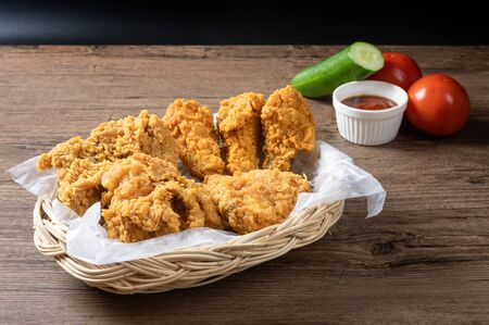 Crispy fried chicken in wicker basket serve with cucumber, tomato and ketchup on wooden background.