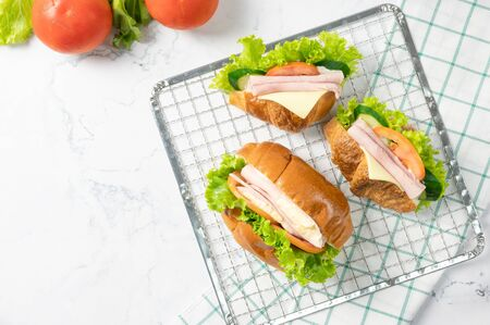 Delicious croissants sandwichs with fresh Ham, cheese, tomato, cucumber, lettuce and Sub sandwich with fresh salad, Ham , cheese served on sieve. white background Top view with copy space. Flat lay.