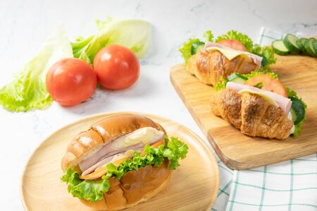 Delicious croissants sandwichs with fresh Ham, cheese, tomato, cucumber, lettuce served on cutting board and Sub sandwich with fresh salad, Ham , cheese served on round wooden plate. white background.
