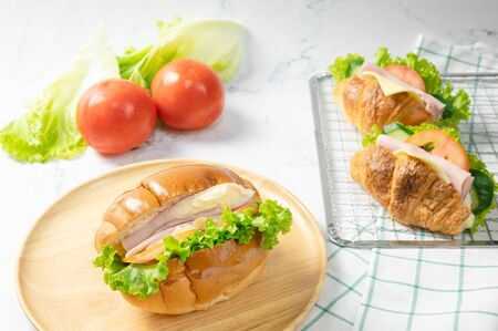 Delicious croissants sandwichs with fresh Ham, cheese, tomato, cucumber, lettuce served on sieve and Sub sandwich with fresh salad, Ham , cheese served on round wooden plate. white background. Foto de archivo