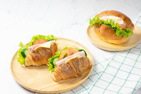 Delicious croissants sandwichs with fresh Ham, cheese, tomato, cucumber, lettuce and Sub sandwich with fresh salad, Ham , cheese served on round wooden plate. white background. Foto de archivo