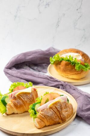 Delicious croissants sandwichs with fresh Ham, cheese, tomato, cucumber, lettuce and Sub sandwich with fresh salad, Ham , cheese served on round wooden plate. white background. Foto de archivo - 149797545