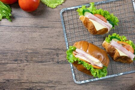 Delicious croissants sandwichs with fresh Ham, cheese, tomato, cucumber, lettuce and Sub sandwich with fresh salad, Ham , cheese served on sieve. wooden background Top view with copy space. Flat lay. Foto de archivo
