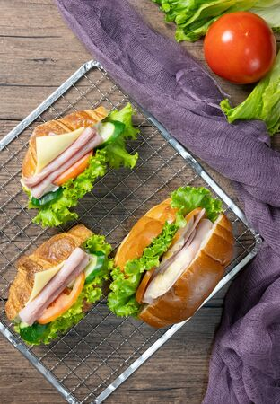 Delicious croissants sandwichs with fresh Ham, cheese, tomato, cucumber, lettuce and Sub sandwich with fresh salad, Ham , cheese served on sieve. wooden background Top view. Flat lay.