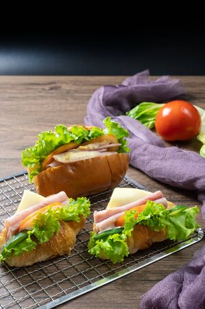 Delicious croissants sandwichs with fresh Ham, cheese, tomato, cucumber, lettuce and Sub sandwich with fresh salad, Ham , cheese served on sieve. wooden background.