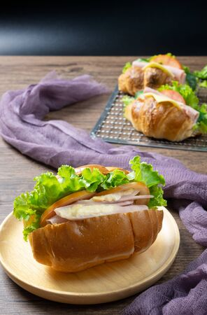 Delicious croissants sandwichs with fresh Ham, cheese, tomato, cucumber, lettuce served on sieve and Sub sandwich with fresh salad, Ham , cheese served on round wooden plate. wooden background.