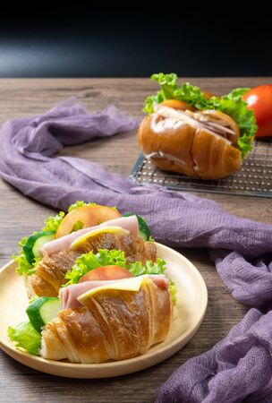 Delicious croissants sandwichs with fresh Ham, cheese, tomato, cucumber, lettuce served on round wooden plate and Sub sandwich with fresh salad, Ham , cheese served on sieve. wooden background
